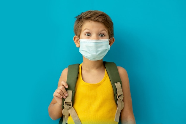 Schooljongen in een medisch masker met een rugzak. terug naar school.
