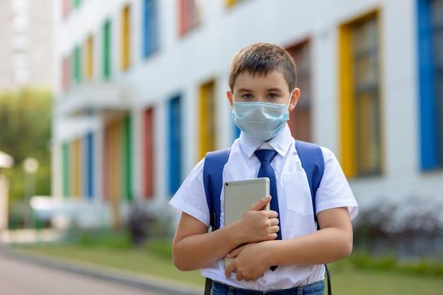 Schooljongen in een wit overhemd, blauwe stropdas en een rugzak