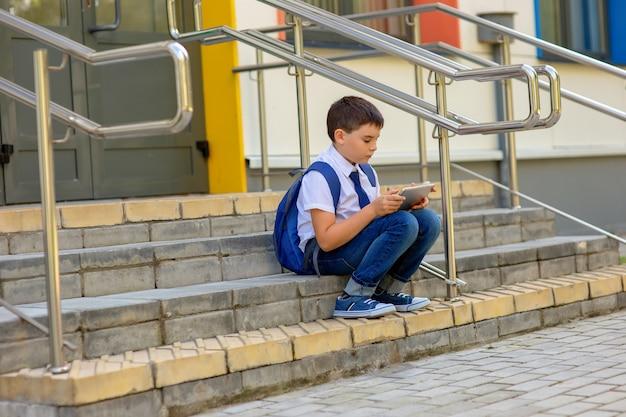 Schooljongen in een wit overhemd met een blauw jasje zit op de trap en speelt met een grijze tablet