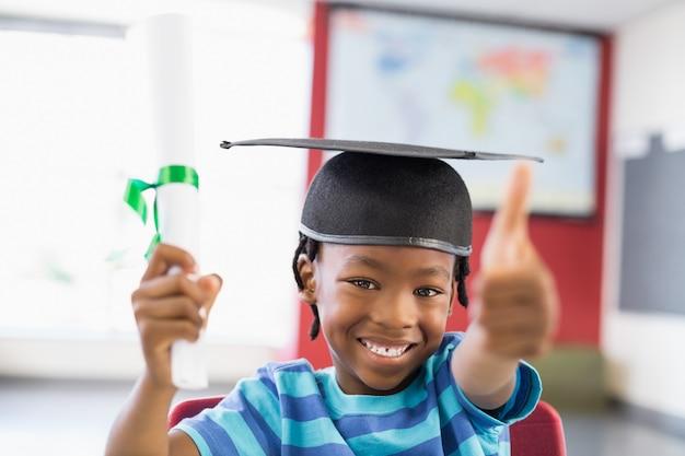 Schooljongen in het certificaat van de mortierraadholding in klaslokaal