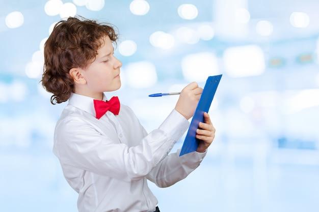 Schooljongen in kostuum en leeg document blad in klembord