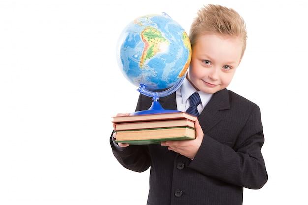 Schooljongen in kostuum met bol op boeken. klaar terug naar school.