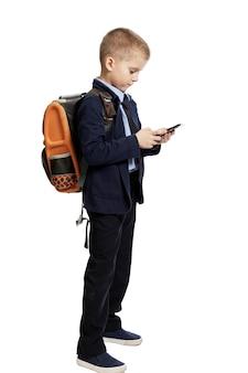 Schooljongen in uniform met een rugzak met een telefoon in zijn hand staat.