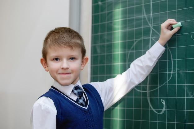 Schooljongen in uniform schrijft met krijt op een schoolbestuur. school basisonderwijs. selectieve aandacht.