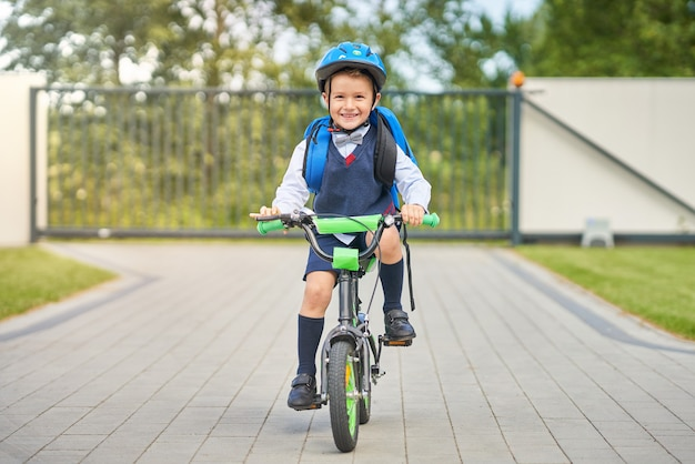 Schooljongen in veiligheidshelm fiets met rugzak