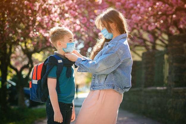 Schooljongen is klaar om naar school te gaan. moeder zet een veiligheidsmasker op het gezicht van haar zoon. terug naar school-concept.
