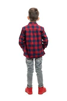 Schooljongen jongen in spijkerbroek en een overhemd staat. volledige hoogte. achteraanzicht. geïsoleerd op witte achtergrond. verticaal.