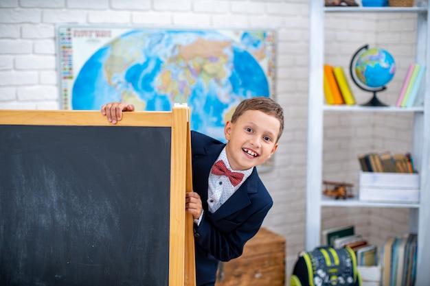 Schooljongen kijkt uit van achter zwarte schoolbord in de klas.