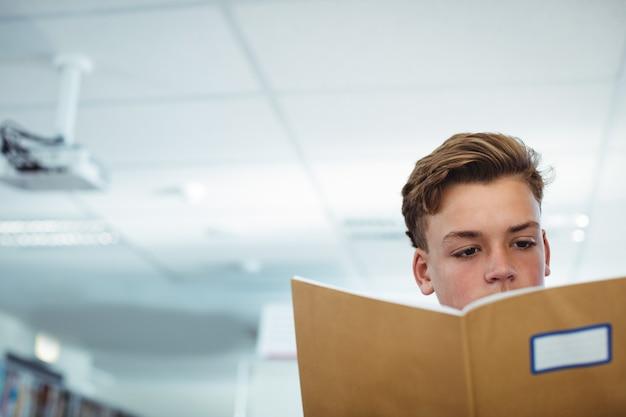 Schooljongen leesboek in bibliotheek