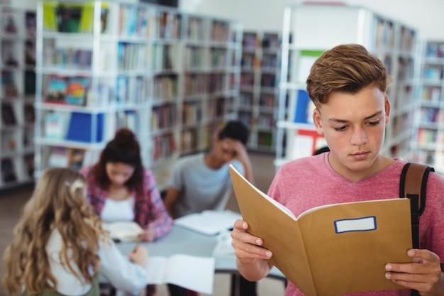 Schooljongen leesboek met zijn klasgenoten studeren