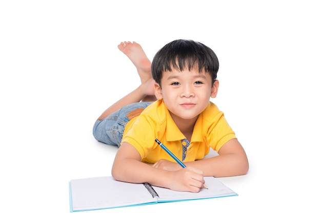 Schooljongen liggen en schrijven in notitieblok.