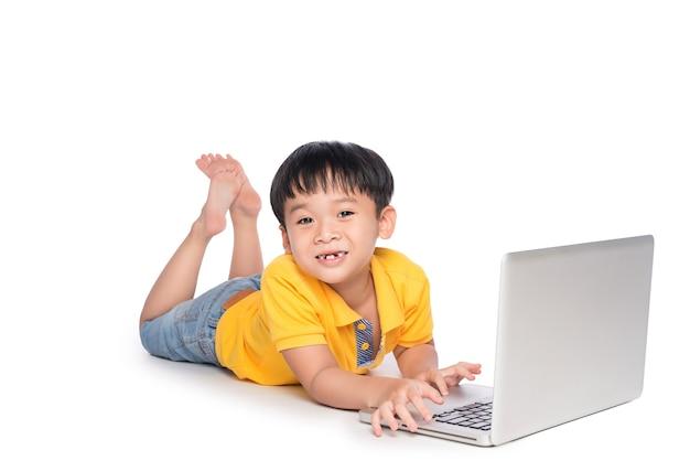 Schooljongen liggen en typen op laptop.