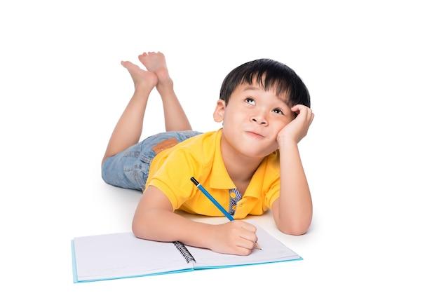 Schooljongen liggend op een vloer, opzoeken en schrijven in notitieblok.