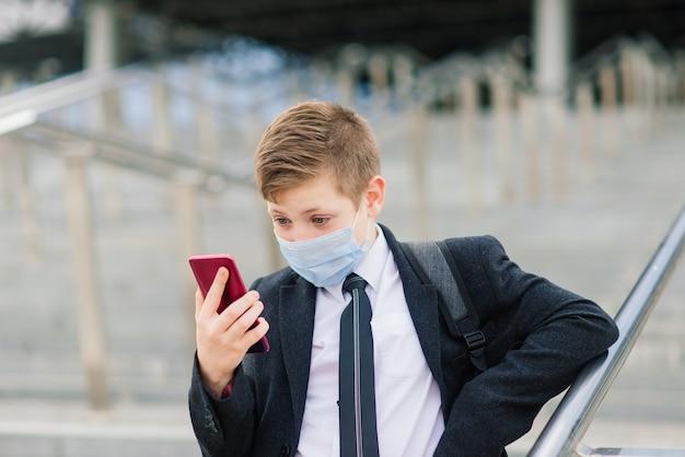 Schooljongen loopt de school uit met een beschermend masker in de stad