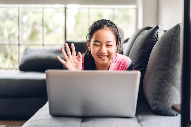 Schooljongen meisje leren en kijken naar laptopcomputer huiswerk studeren kennis met online onderwijs e-learning systeem. kinderen videoconferentie met leraar tutor thuis