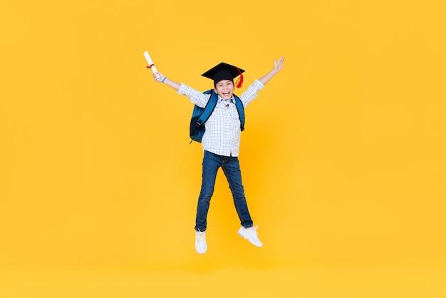 Schooljongen met afgestudeerde pet glimlachen en springen