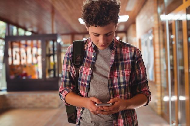 Schooljongen met behulp van mobiele telefoon in gang op school