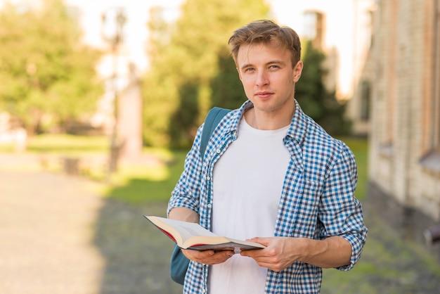Schooljongen met boek in park