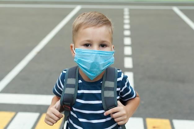 Schooljongen met een medisch masker, met een rugzak op de ruimte van het schoolgebouw, met een duim omhoog