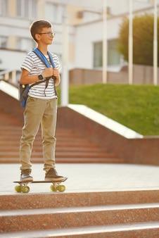 Schooljongen met een skate en rugzak