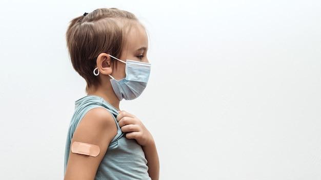 Schooljongen met gezichtsmasker met arm met verband coronavirus-vaccinatiecampagne