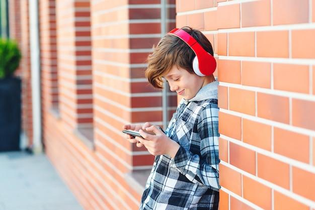 Schooljongen met koptelefoon en smartphone. student luistert muziek tijdens pauze. terug naar schoolconcept.