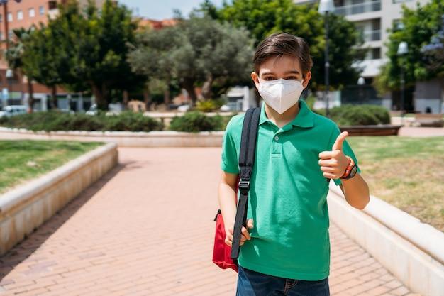 Schooljongen met masker om zichzelf te beschermen tijdens de pandemie van het coronavirus
