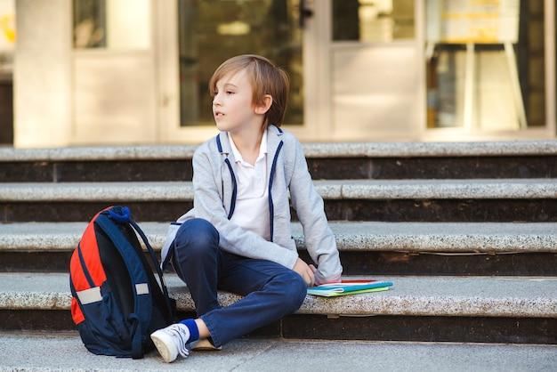 Schooljongen met rugzak en boeken die op de trap zitten.