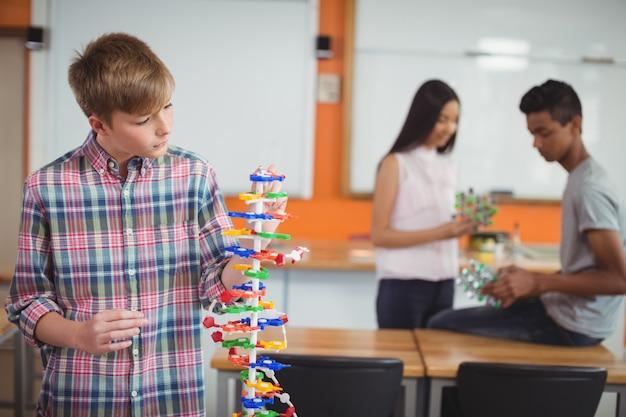 Schooljongen onderzoekt het molecuul-model in laboratorium