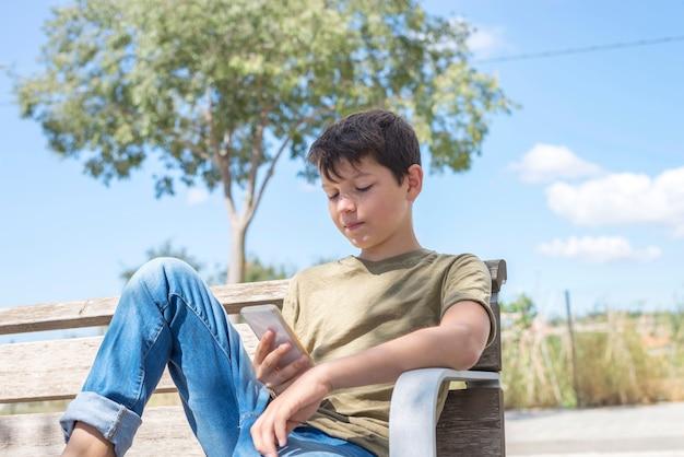 Schooljongen op bank die onderbreking neemt mobiel gebruiken