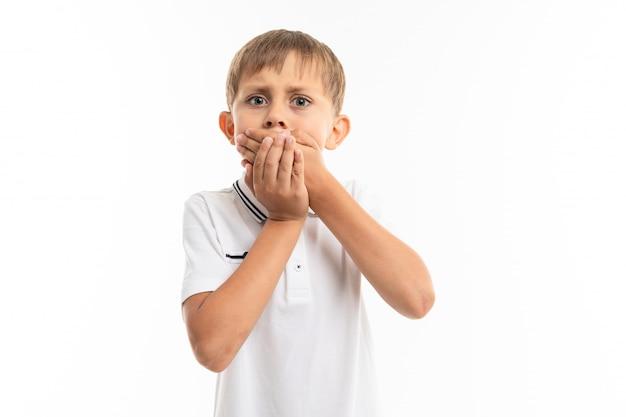 Schooljongen op een witte ondergrond sluit zijn mond met zijn handen, is bang om uit te flappen, emotioneel portret