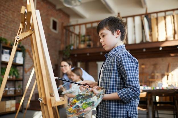 Schooljongen schilderen op ezel