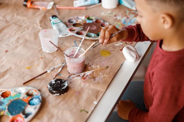 Schooljongen schilderen op papier met kleurrijke verf