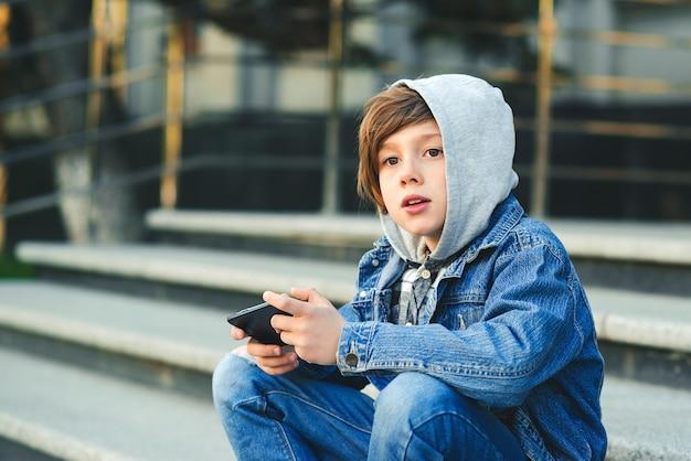 Schooljongen speelspel op smartphone na school. technologie, lifestyle, vrije tijd. kinderen zijn verslaafd aan online games en video's.