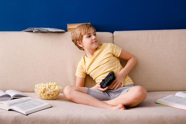 Schooljongen speelt videogames houdt een gamepad vast en eet popcorn in plaats van lessen te leren