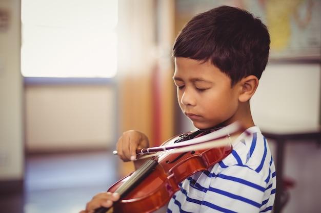 Schooljongen viool spelen in de klas