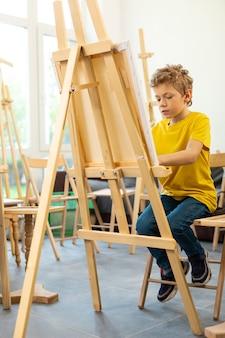 Schooljongen voelt zich vrolijk tijdens het schilderen op de kunstacademie