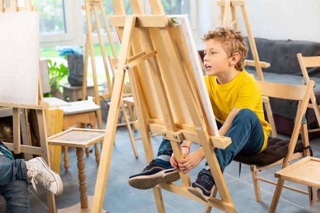 Schooljongen zit in de buurt van schildersezel in de kunstacademie