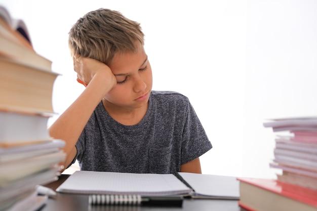 Schooljongen zit onder stapel boeken