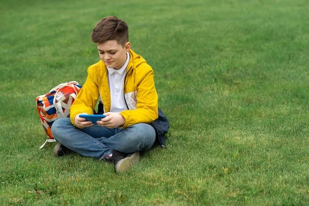 Schooljongen zit op het gazon met slimme telefoon
