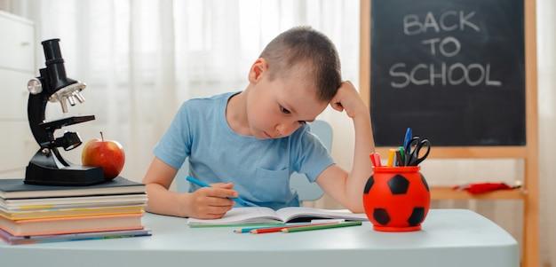 Schooljongen zitten thuis klaslokaal liggend bureau gevuld met boeken trainingsmateriaal schoolkind slapen lui verveeld