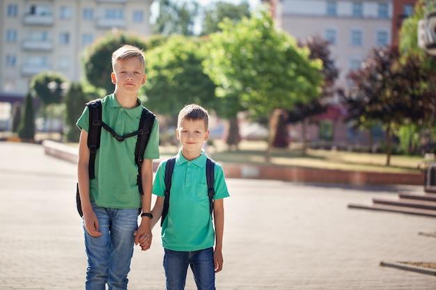 Schooljongens met rugzakken naar school gaan. kinderen en onderwijs in de stad.