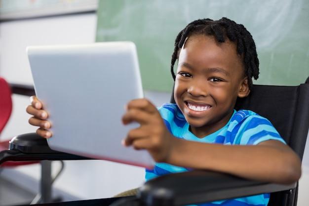 Schooljongenzitting op rolstoel en het gebruiken van digitale tablet