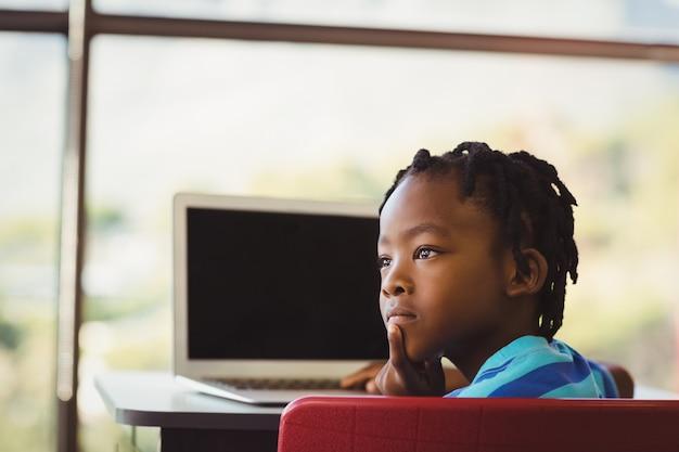 Schooljongenzitting op stoel en het gebruiken van laptop op school