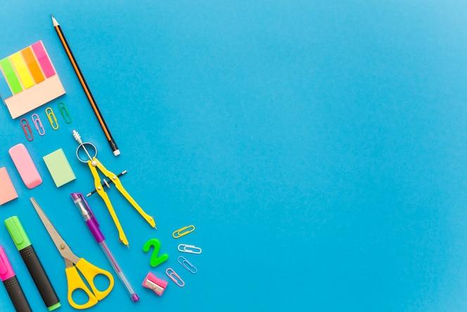 Schoolkantoorbehoeften op blauwe achtergrond worden geïsoleerd die