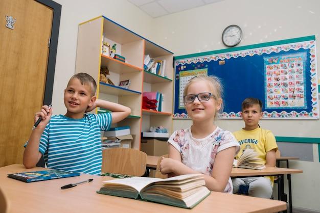 Schoolkids zitten in de klas glimlachen