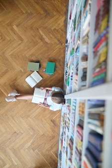 Schoolkind dat een boek leest op de bibliotheekvloer