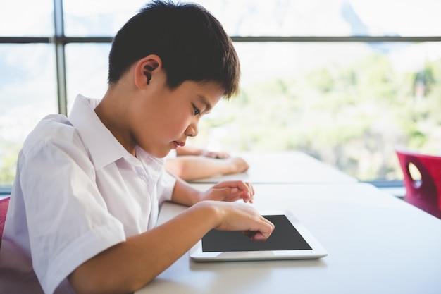 Schoolkind die digitale tablet in klaslokaal gebruiken