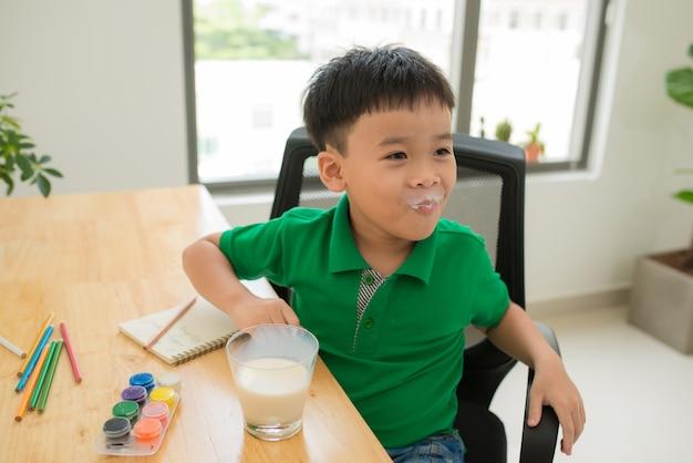 Schoolkind huiswerk maken en melk drinken