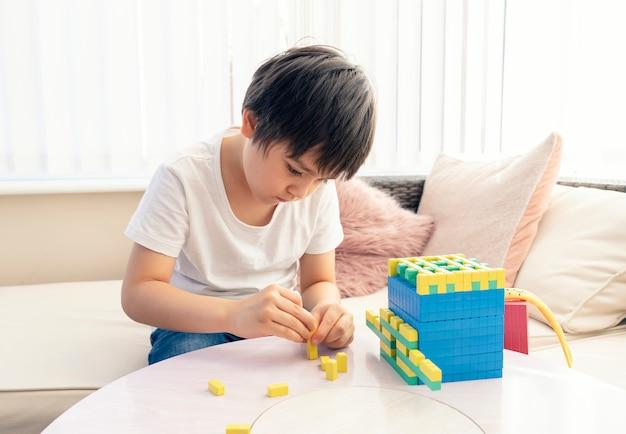 Schoolkind met behulp van plastic bloknummering, kindjongen die wiskunde bestudeert door kleurstapelbox, montessori-klaslokaalmateriaal voor kinderen die thuis wiskunde leren, thuisonderwijs, afstandsonderwijs